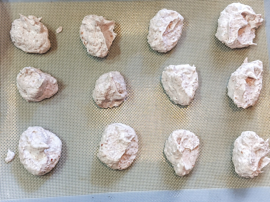 strawberry walnut meringue cookies on silicone mat and baking tray