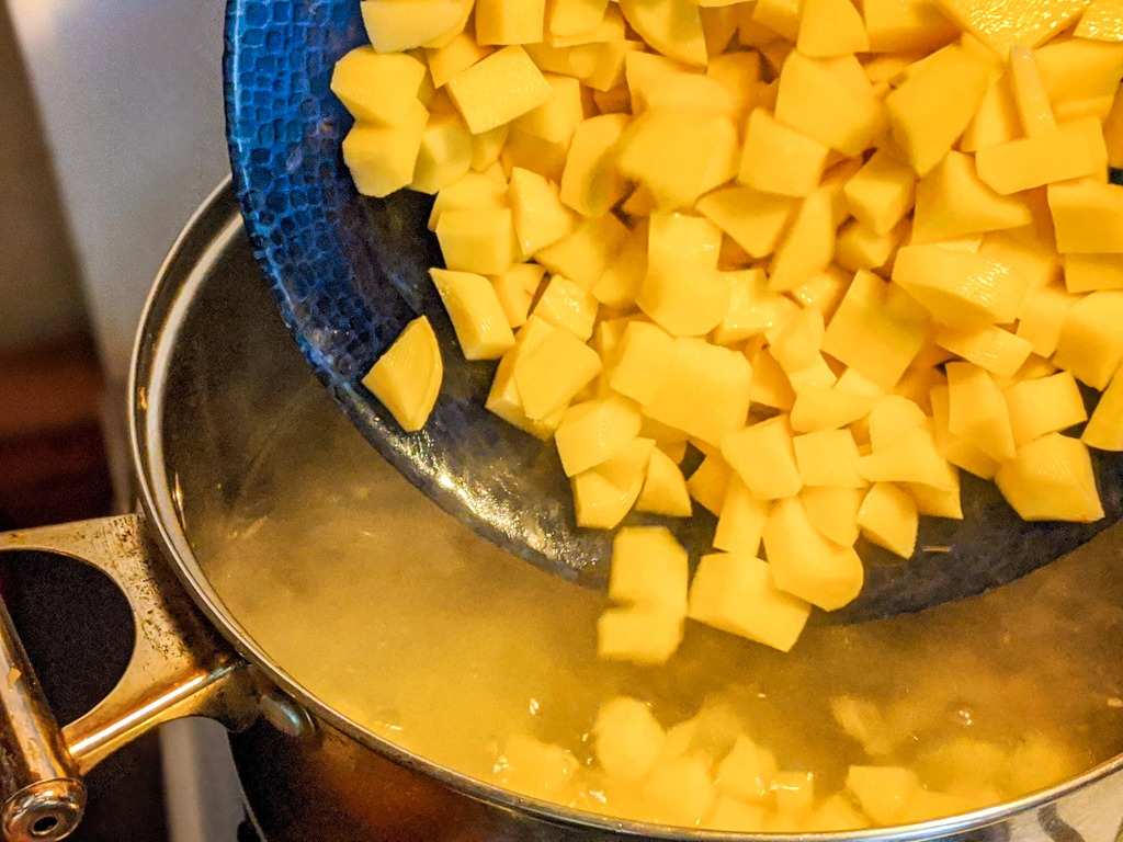 adding potatoes to the soup pot