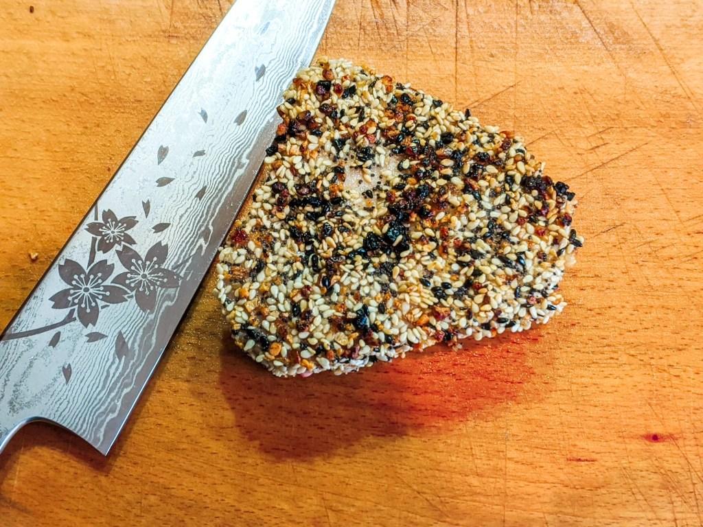 Sesame crusted ahi tuna next to a japanese knife