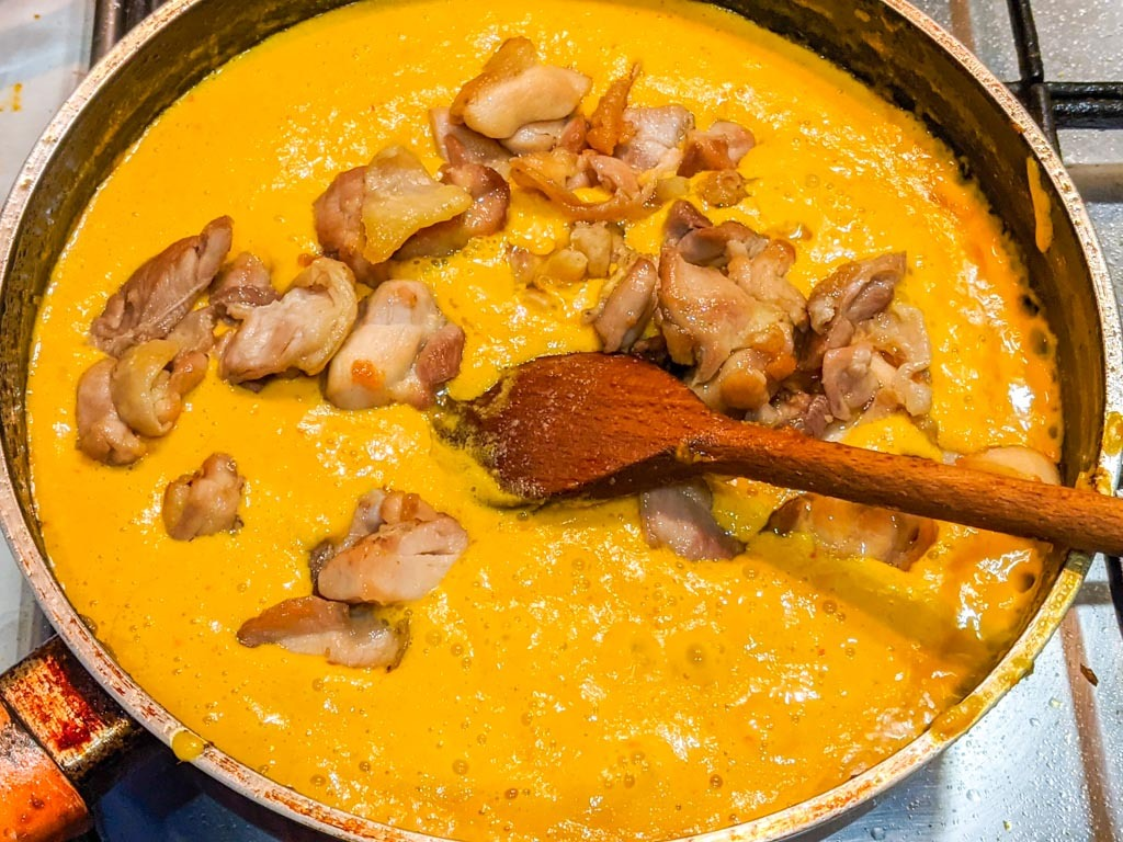 adding chicken to the mango curry sauce