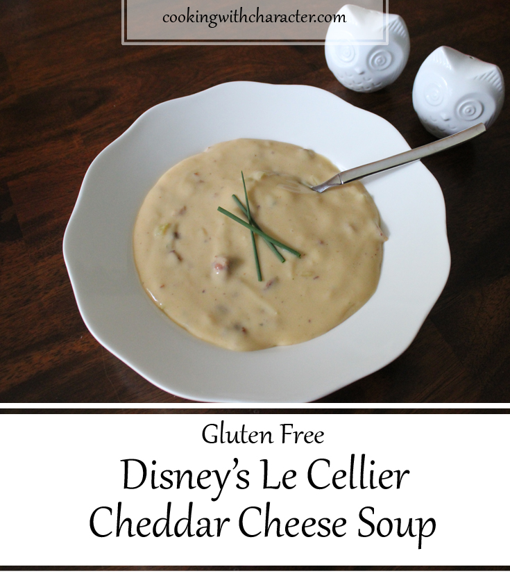 Le Cellier Cheese soup in a bowl with a spoon and chive garnish.