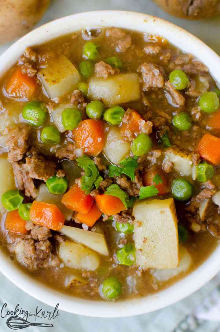 Instant Pot Ground Beef Stew made with potato chunks, carrots, peas and ground beef which are swimming in a thick delicious gravy.