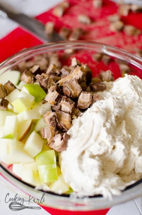 apples, candy bar and cool whip mixture big tossed together in a bowl.