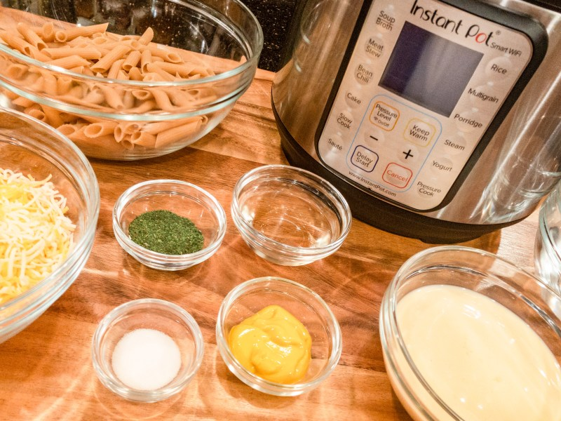 ingredients for champagne dill macaroni and cheese, including mustard, dill, champagne, salt, evaporated milk, shredded cheese, gluten free pasta, and an instant pot, all sitting on a large wood cutting board