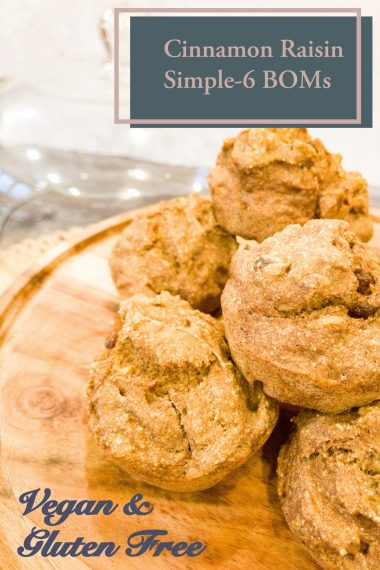 healthy simple-6 banana oat muffins with cinnamon, raisins, and walnuts, on a wood pedestal sitting on a dark wood counter in front of a concrete wall