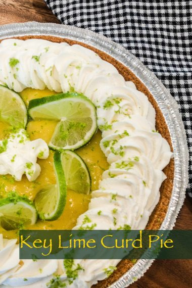 key lime curd pie with gluten free graham cracker crust, whipped cream, lime slices, and lime zest