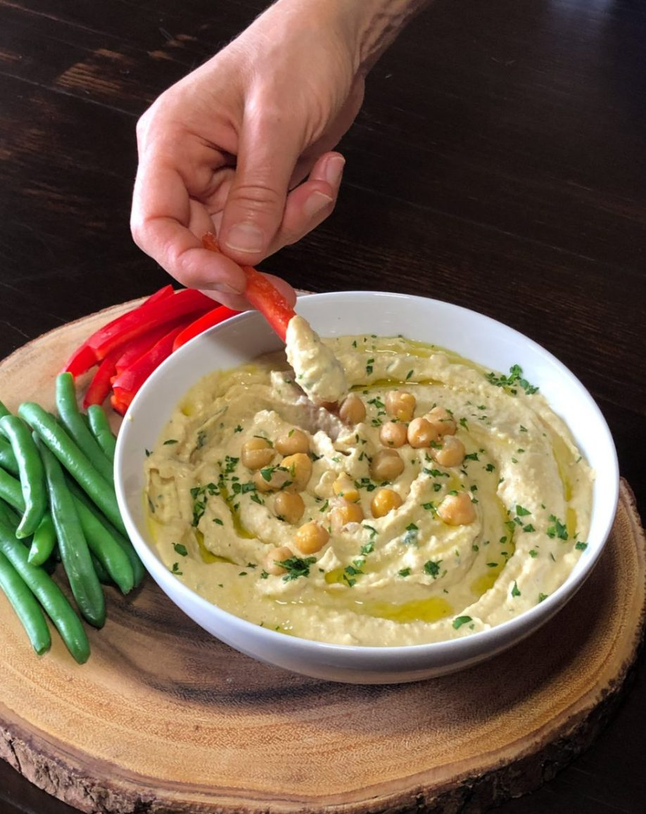 dipping red bell pepper into chickpea hummus