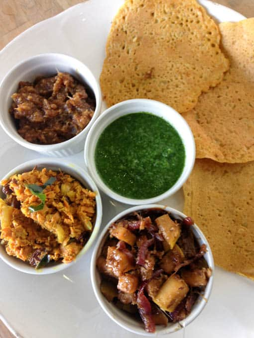 photo of four Indian chutneys and chickpea flatbread