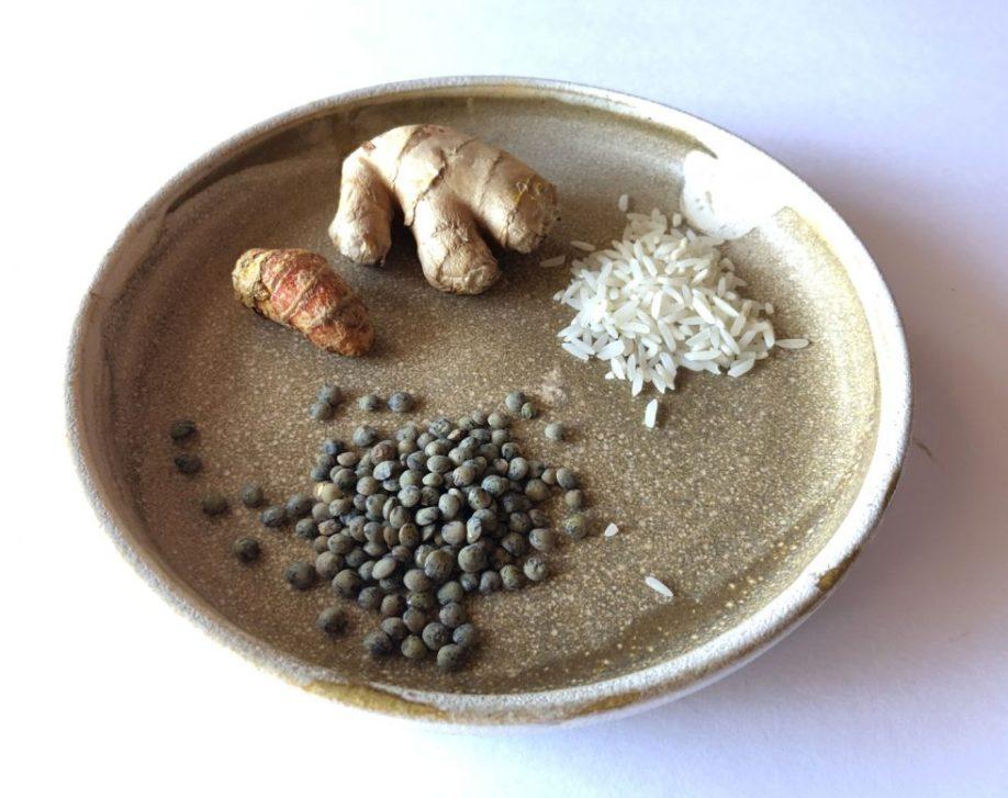 Kitchari ingredients green lentils, basmati rice, ginger, and turmeric on a handmade plate