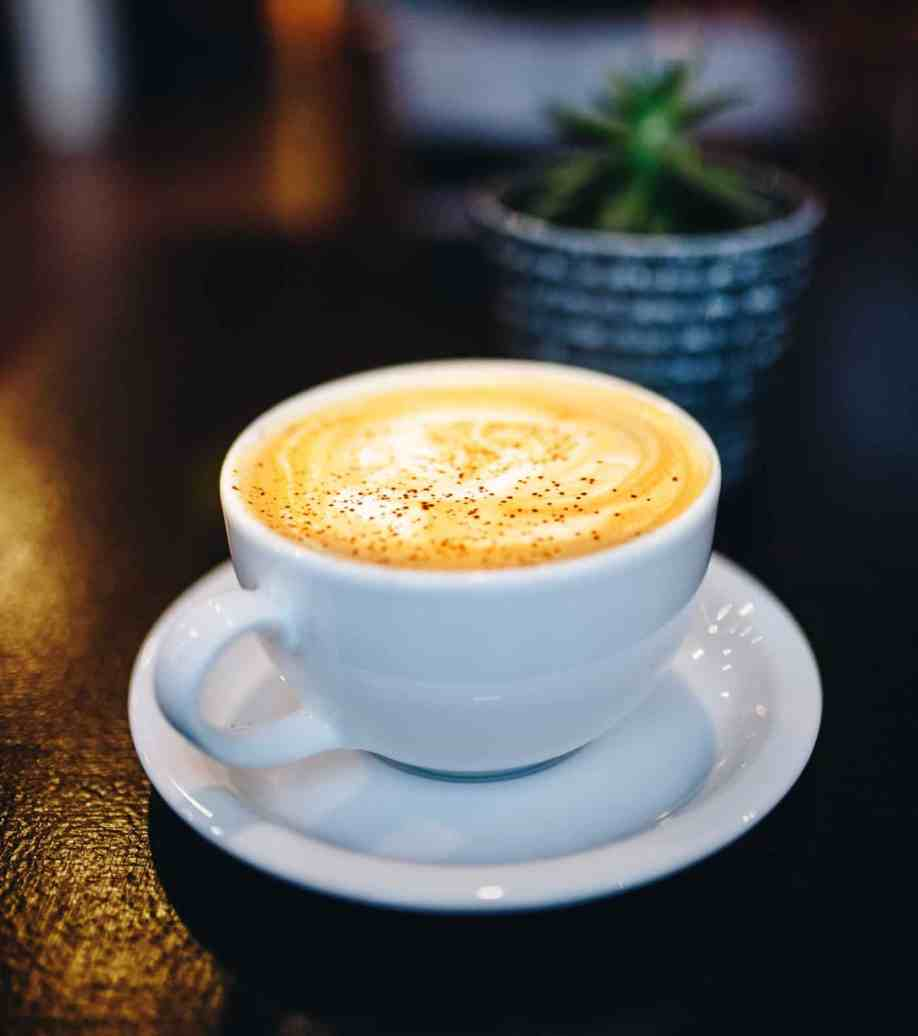 photo of golden milk latte in white cup with saucer by Cook Love Heal by Rachel Zierzow