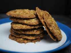 Stacks of thin-crispy oatmeal raisin cookies on a white and blue plate.