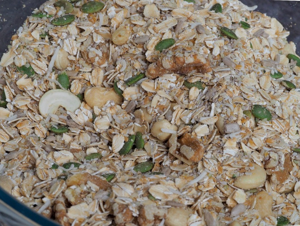 A mix of granola ingredients in a glass mixing bowl