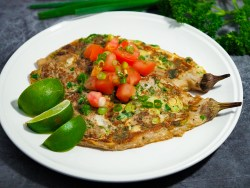 Eggplant omelette, top with diced tomatoes, thinly sliced scallion and 3 slices of lime on a white dinner plate