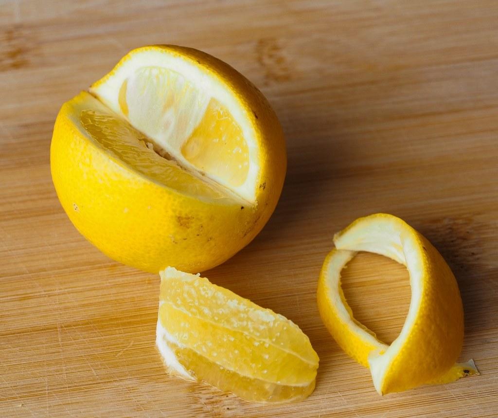 whole lemon, Lemon pith and a section of lemon flesh on a bamboo chopping board