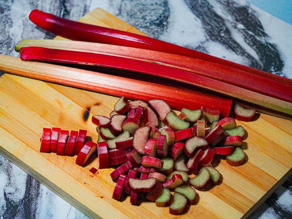 Sliced rhubarb and whole stalks of rhubarb on a bamboo chopping board .