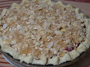 Raw pie dough on a baking dish filled with strawberry-rhubarb filling topped with almond and oat streusel toppings