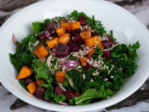Chopped kale, caramelized sweet potatoes, thinly sliced red onion and sunflower seeds in a white serving bowl.