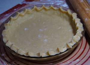 Crimp pie crust in a glass baking dish on top of a silicone mat