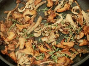 Caramelized mixed mushroom with thyme in a sautee pan.