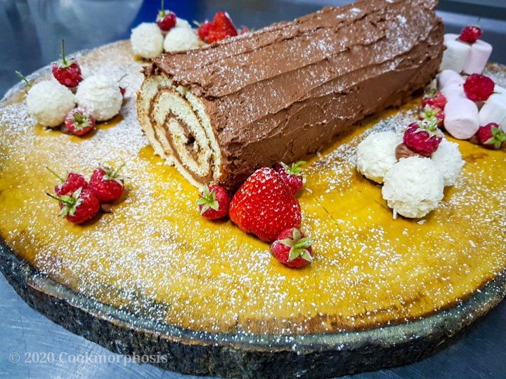 chocolate yule log cake decorated with strawberry, marshmallow, and white chocolate
