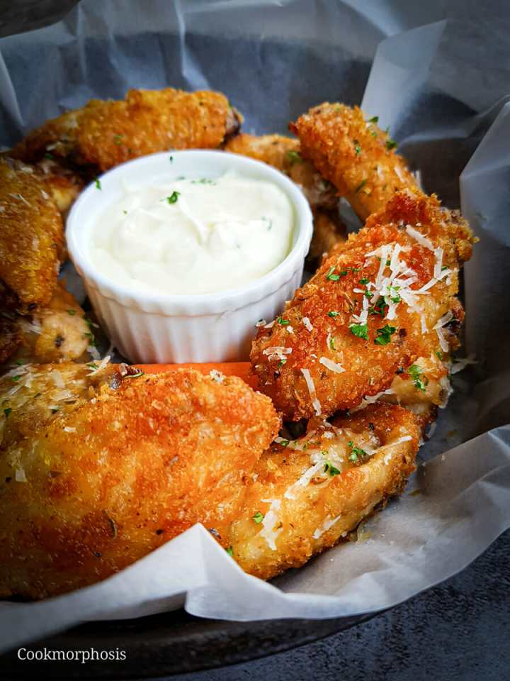 parmesan chicken wings are the best super bowl appetizers, they are garnished with shredded parmesan cheese and chopped parsley
