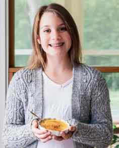 young girl smiling and holding creme brulee