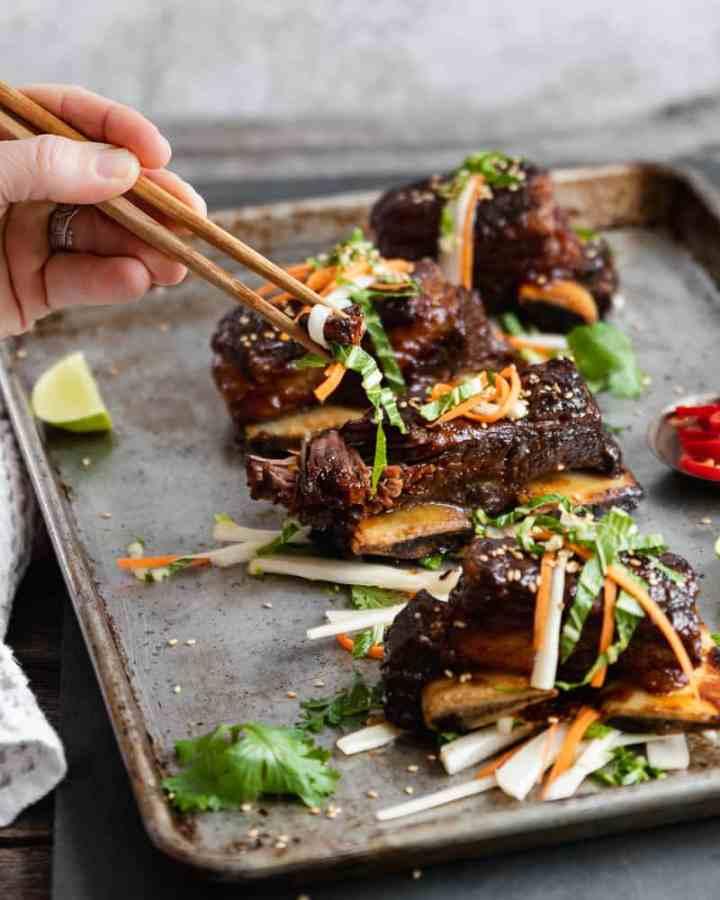 chop sticks holding asian beef short ribs