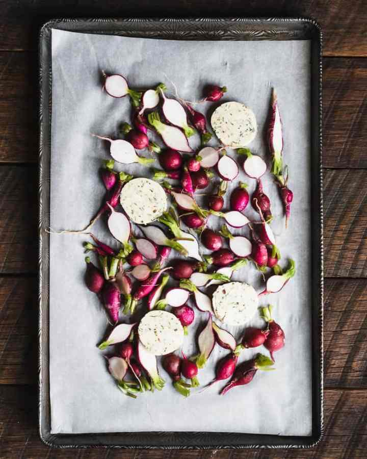 radishes and butter on parchment lined sheet tray before baking