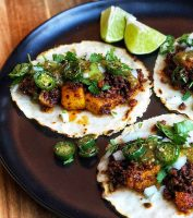 Chorizo and potato tacos on corn tortillas with wedges of lime