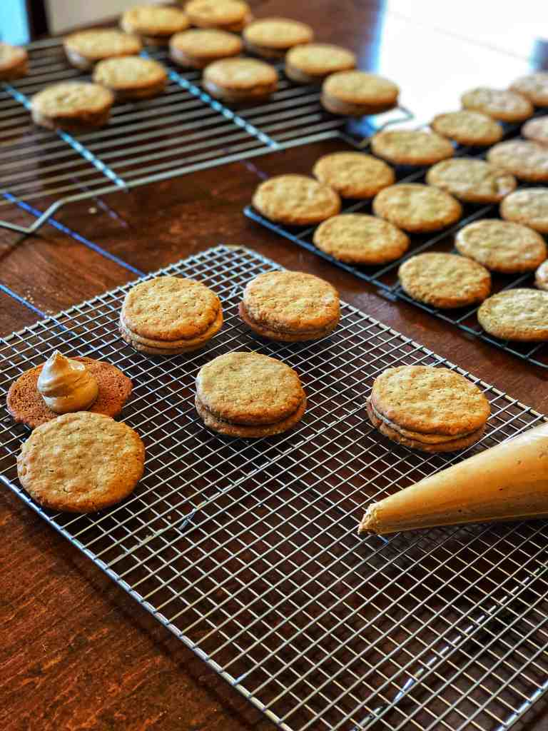 A baking rack containing thin peanut butter cookies and a piping bag filled with peanut butter fluff, ready to pie and make sandwich cookies.