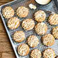 Glazed Maple Butterscotch Cookies on a sheet tray and cooling rack with an extra spoonful of glaze.