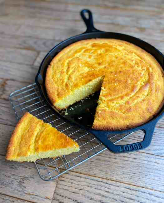 Skillet Cornbread on a wire rack with one slice cut out