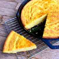 Cast iron skillet of cornbread with one triangular slice taken out.