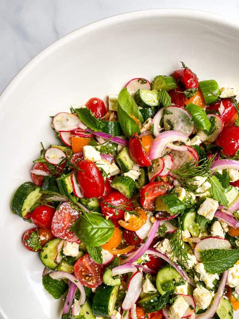 Greek Salad with herb marinated feta is filled with fresh tomatoes and cucumbers in a lemon and herb dressing