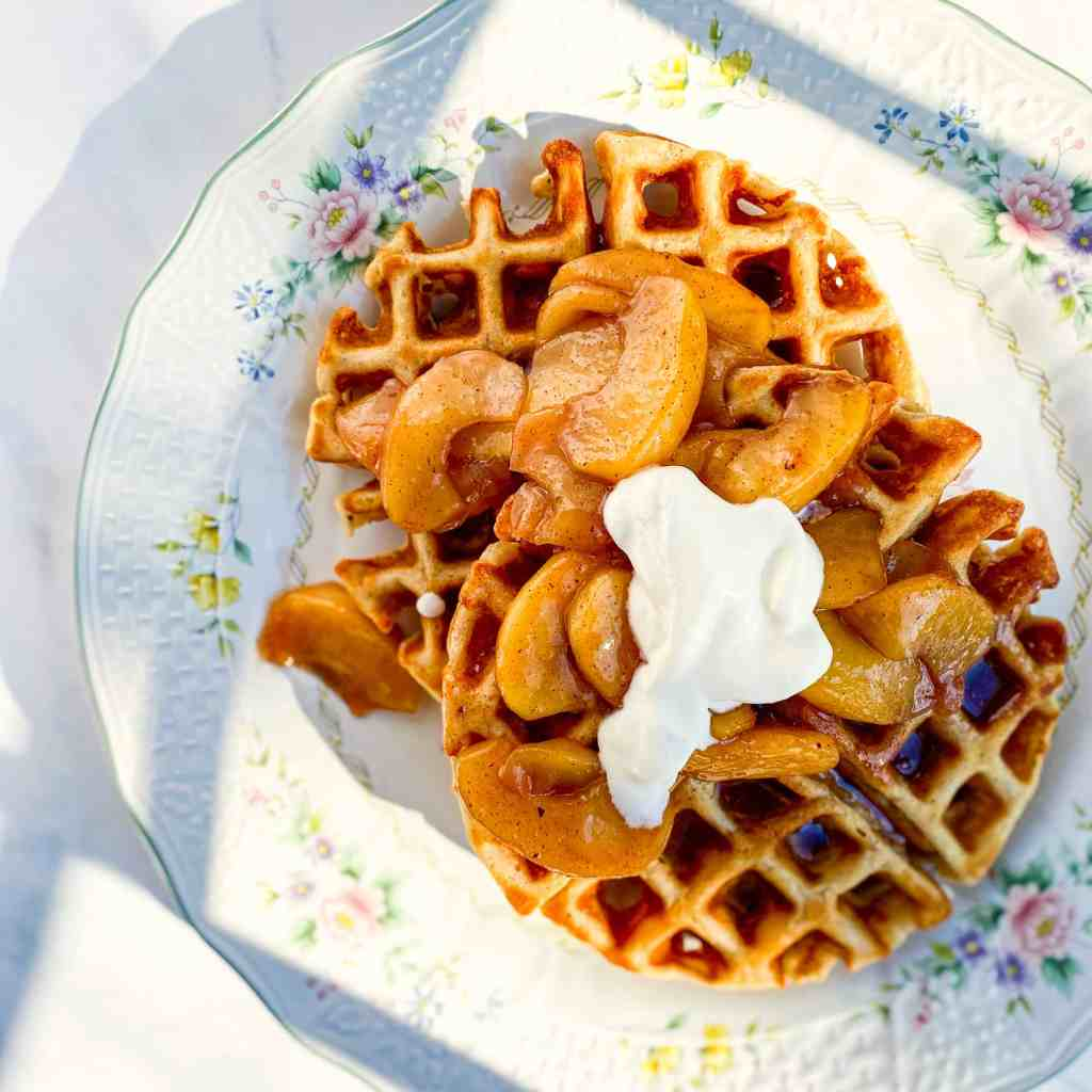 Chai Spiced Waffles on a flowered plate topped with Maple Cinnamon Apples ands softly whipped Cream