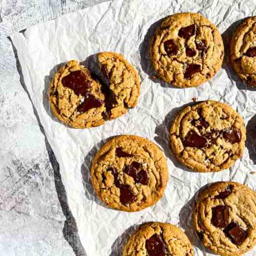 Peanut butter cookies with melty chopped chocolate, laying on crumpled parchment paper