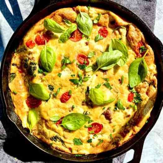 Cast iron pan of Italian Frittata, with fresh basil garnish.