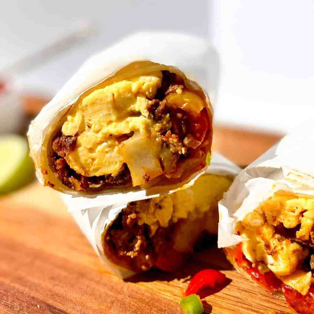 Parchment paper wrapped Chorizo, Potato, and Egg Breakfast Burrito on a wooden cutting board