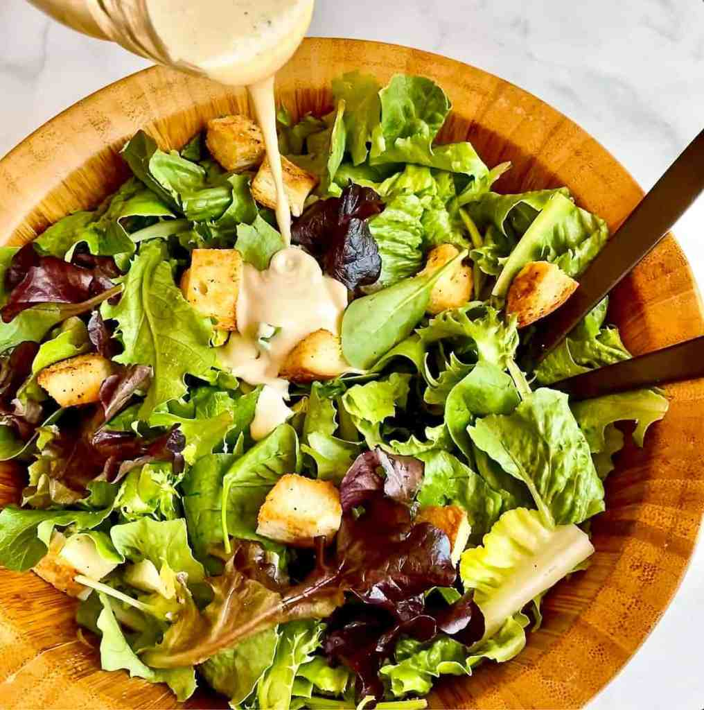 Pouring Creamy Caesar Dressing over a bed of greens.