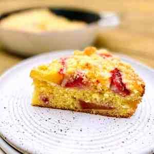 A slice of Strawberry-Peach Cornbread Buckle on a white plate