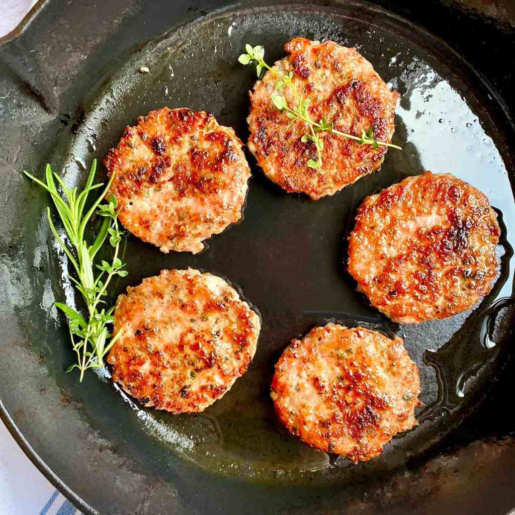 Ground Breakfast Sausage patties in a cast iron skillet with fresh herbs.