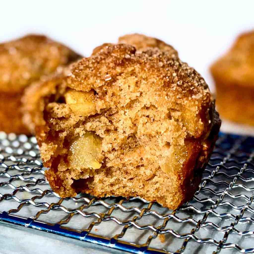 An apple cinnamon crunch muffin on a baking rack.
