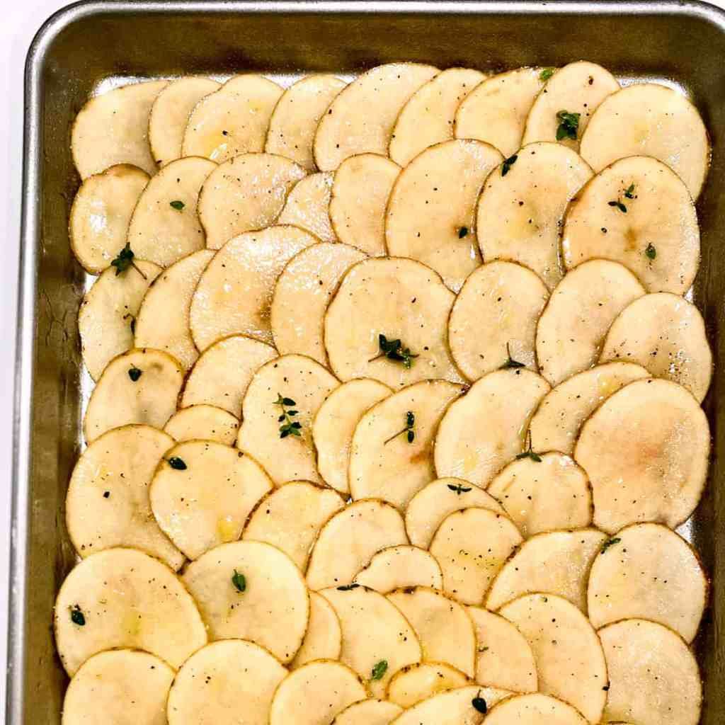 Very thinly sliced raw potatoes on a sheet pan, seasoned with olive oil and fresh thyme.