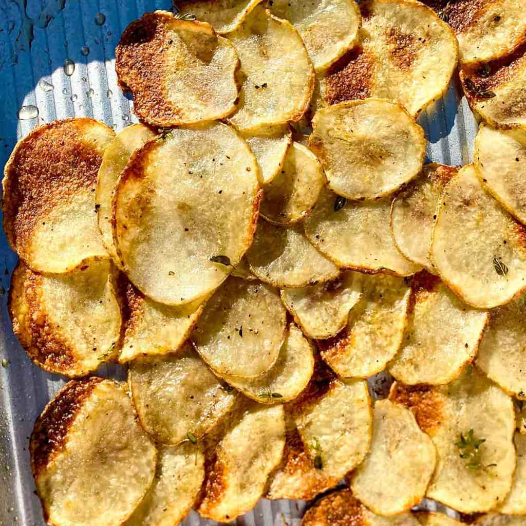 A sheet pan with very thinly sliced baked potatoes