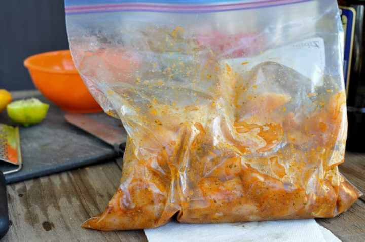 raw chicken strips in a citrus marinade in a baggie
