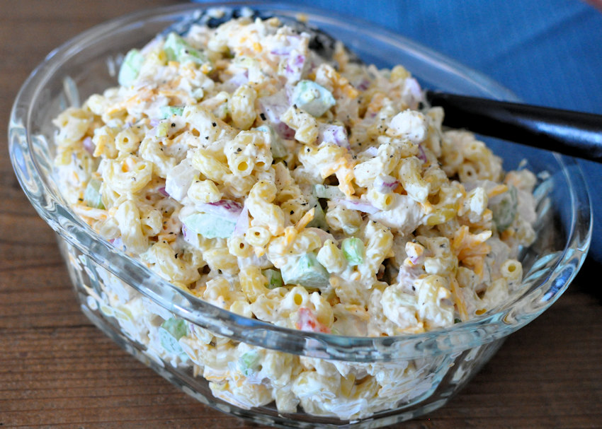 Rotisserie Chicken Macaroni Salad in a clear bowl with a black spoon.