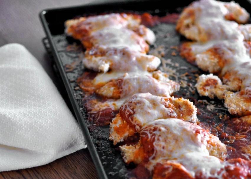 Easy Baked Chicken Parmesan just baked still on dark baking pan