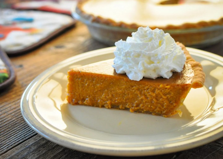 a slice of fresh butternut squash pie topped with whipped cream on a cream colored plate