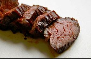 Beef cooked in the sous-vide method.  Done on the outside, tender in the middle.
