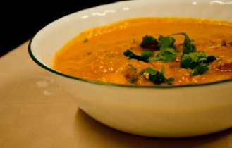 Butter chicken garnished with coriander leaves